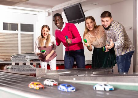 Cheerful men and women play together with slot car racing track Stock Photo