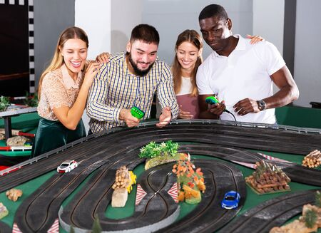Two young couples playing with slot car model racing track