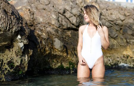 Portrait of young female in swimsuit posing near stones at sea shore