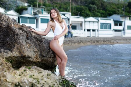 Young pretty girl  in swimsuit and hat posing near stones at  sea shore
