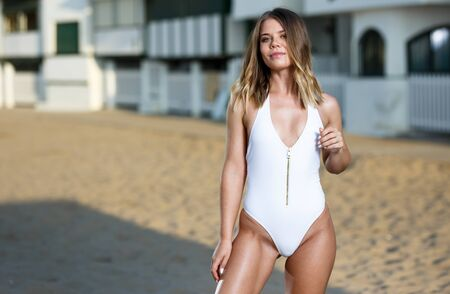 Portrait of young female in swimsuit posing near hotel at sea shore