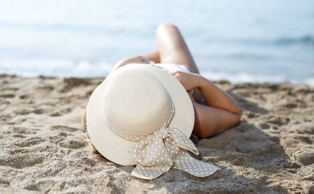 Portrait of beauty girl in hat  relaxation and taking sunbath at sandy beach Banco de Imagens