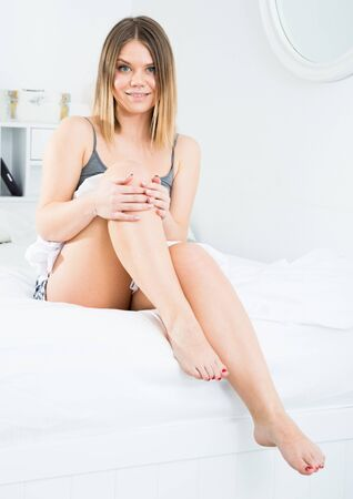 Sexy female is posing playfully on bed and holding leg in bedroom in home interior