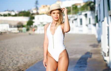 Closeup of  sexy girl in swimsuit and hat posing near buildings at  sea shore
