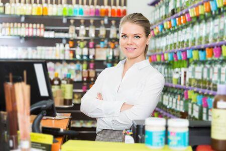 Exitosa vendedora joven feliz de pie en la tienda de perfumes Foto de archivo