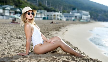 Cheerful sexy girl  in swimsuit and sunglasses sitting at sand at  sea shore