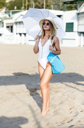 Portrait of young female in swimsuit with umbrella and bag walking at beach Banco de Imagens