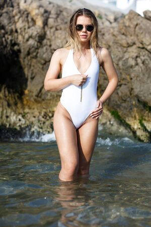 Young sexy woman in swimsuit and sunglasses near stones at  sea shore Banco de Imagens