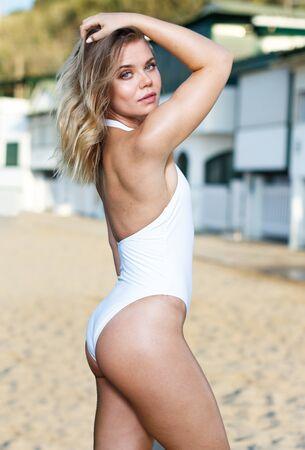 Closeup of  sexy female  in swimsuit posing near buildings at  sea shore Banco de Imagens