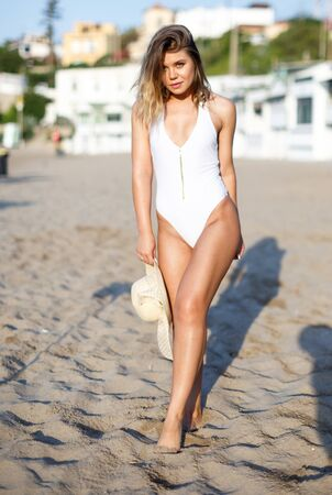 Young beauty female  in swimsuit with hat posing near buildings at  sea shore Banco de Imagens