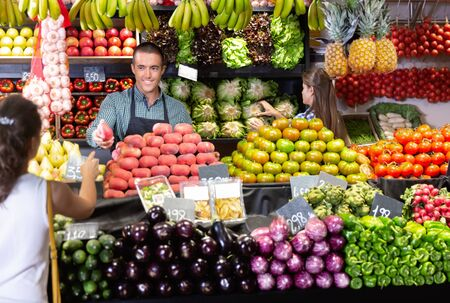 Friendly  positive cheerful smiling man and woman laying out vegetables and fruits in shop Reklamní fotografie