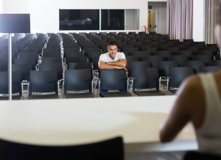 Male participant of event waiting of start in conference hall