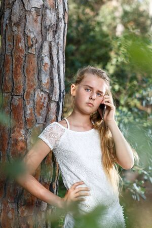 Serious teenage  girl using smartphone near tree at sunny park outdoor