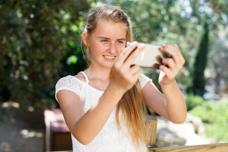Portrait of  teenage cute girl  making photo with smartphone at sunny day outdoor Banco de Imagens