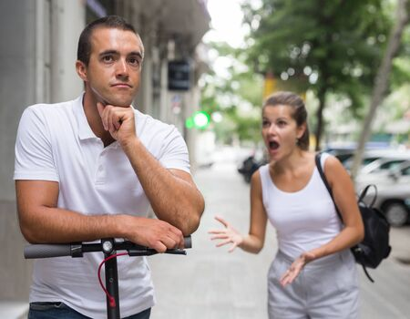 Young woman swearing offended man with electric scooter