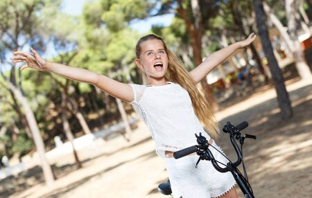 Emotional  teen girl standing near bicycle ready to go on park ride at sunny day