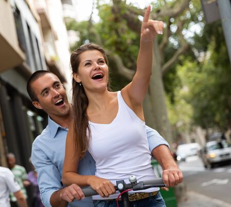 Cheerful couple riding electro scooter on streets of Barcelona