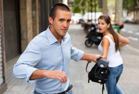 Male thief stealing woman bag on street of city