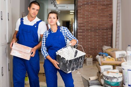 Diligent friendly smiling man and woman in work overalls doing finishing work in room of public space