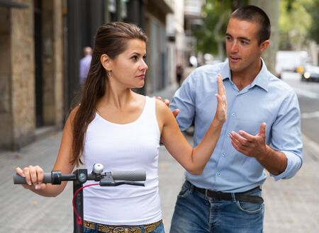 Offended girl quarreling with man during riding electro scooter in city