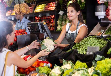 Polite shop assistans selling fresh fruits and vegetables to woman Reklamní fotografie