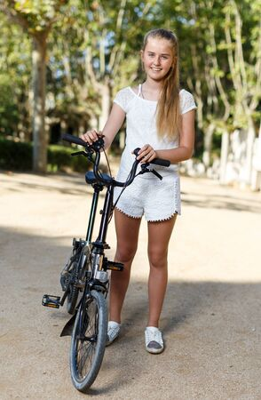 Smiling teen girl standing near bike ready to go on park ride at sunny day