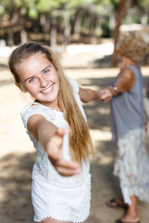Portrait of  teen girl girl pulling hand and keep grandmother on hand in green park Banco de Imagens