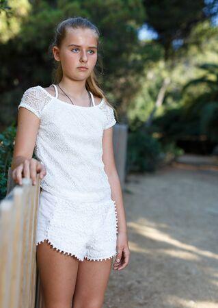 Portrait of tired teen girl standing near fence  in summer green park outdoor Banco de Imagens