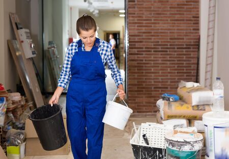 Young friendly  positive female worker holding buckets during doing finishing work in room Reklamní fotografie