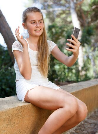 Cheerful teen girl making selfie with phone  in summer green park at sunny day Banco de Imagens