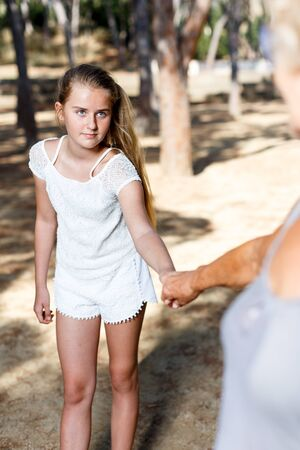 Portrait of  teen girl keep grandmother on hand in summer green park