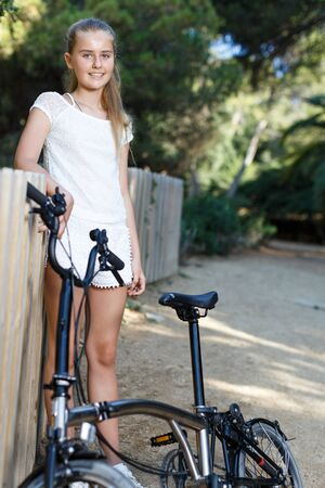 Teen girl standing near fence with bicycle ready to go on park ride at sunny day Banco de Imagens