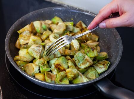 Fried peeled artichokes in a pan