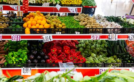 Large assortment of fresh colorful fruits and vegetables in wicker trays on shelves in supermarket