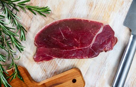 Ingredients for cooking. Slice of fresh raw horse meat fillet on wooden table with rosemary