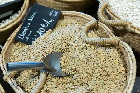 Closeup of dried lentil seeds in wicker basket for sale in store. Organic bulk foods