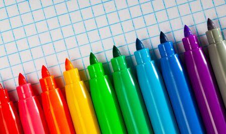 Many various felt tip pens on checkered sheet of paper