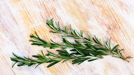 Image of rosemary on wooden background, top view
