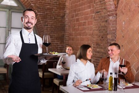 happy man waiter demonstrating country restaurant to visitors Stok Fotoğraf