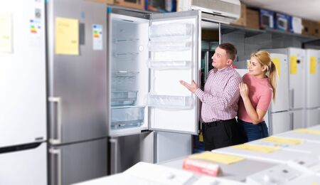 couple choosing fridge in store of household appliances 스톡 콘텐츠