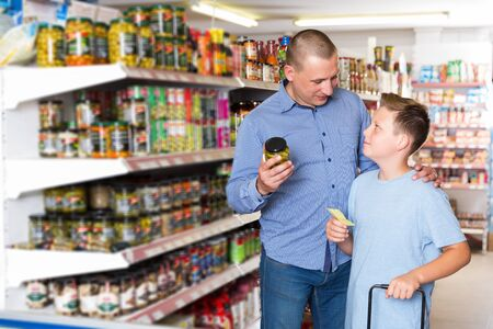 positive adult father doing shopping with preteen boy looking at shopping list while choosing fresh products in food store