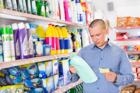 Man looking at shopping list while choosing household detergents in a store