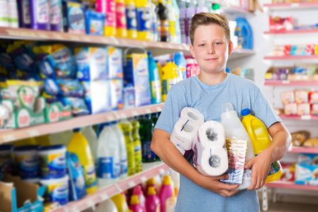 Smiling  boy holding a lot of products after shopping in store