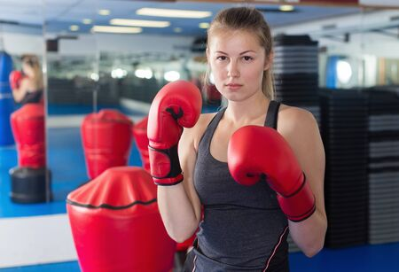 Female boxer is kicking in time training in box gym Stock Photo