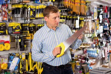 Confident glad cheerful positive man is choosing bucksaw in tools store Imagens
