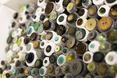 Various buttons for clothes in plastic containers on shelves of sewing store