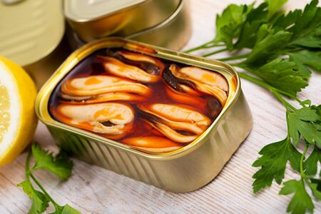 Marinated in oil mussels served in tin with lemon and parsley Stockfoto