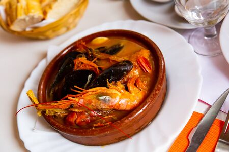 Hearty and spicy Parihuela - Peruvian seafood soup with mussels and prawns Stock Photo - 140510991