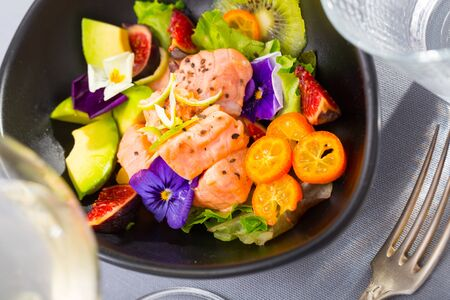 Delicious ceviche of salmon with kiwi fruit, avocado, kumquat and figs garnished with heartsease flowers