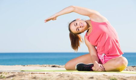 vigorous young woman exercising on exercise mat outdoor at the seaside